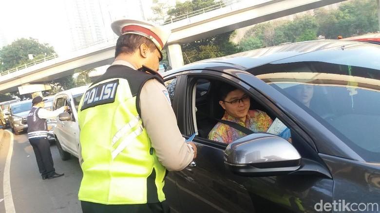 Petugas Kepolisian Mensosialisasikan Uji Coba Ganjil Genap di Tomang